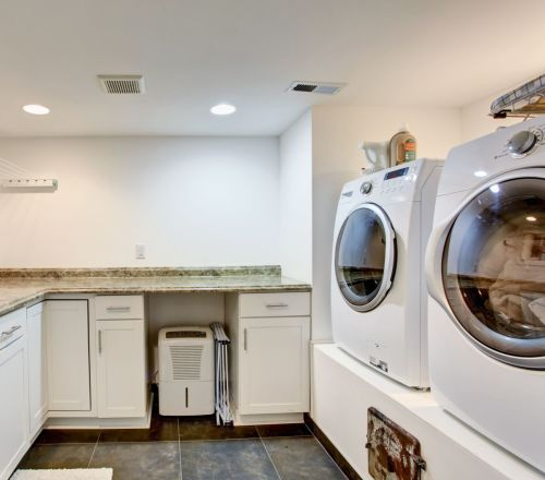 Light laundry room with marble countertops