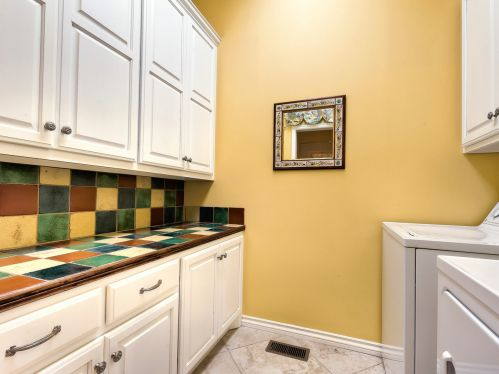 Colorful tiles and yellow on this fun laundry room